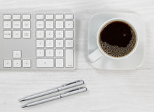 Cup of coffee on top of the office desktop Royalty Free Stock Photos
