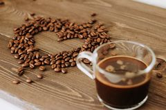 Cup of coffee on a tray and coffee beans in the shape of a heart stock photo