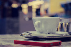 A cup of coffee on a tray and smart phone on a table Stock Image