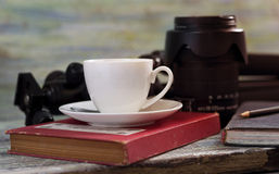 A cup of coffee ,a tripod and lens on wooden table concept for t Royalty Free Stock Photo