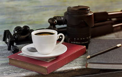 A cup of coffee ,a tripod and lens on wooden table concept for t Stock Photo