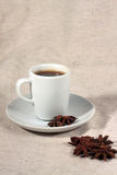 A cup of coffee and truestar anisetree. Against light background Stock Photos