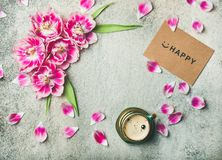 Cup of coffee, tulip flowers and sign happy, copy space. Spring morning concept. Flat-lay of cup of coffee surrounded with pink tulip flowers, petals and sign Royalty Free Stock Photo