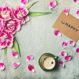 Cup of coffee, tulip flowers and sign happy, square crop. Spring morning concept. Flat-lay of cup of coffee surrounded with pink tulip flowers, petals and sign Stock Images