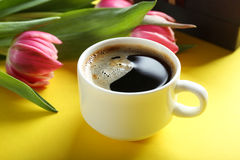Cup of coffee with tulips and gift box on yellow background, clos Stock Photo