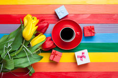 Cup of coffee with tulips and gifts Stock Photos