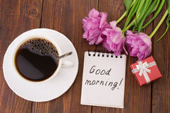 Cup of coffee, tulips and Good morning massage. On wooden background Royalty Free Stock Photo