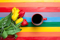 Cup of coffee with tulips. On multicolored background Royalty Free Stock Photography