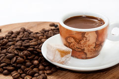 A cup of coffee and Turkish delight on a wooden board and raw co Royalty Free Stock Photo