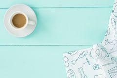 Cup of coffee on turquoise table with white napkin. Cup of coffee on turquoise colored old wooden table with white napkin top view Royalty Free Stock Images