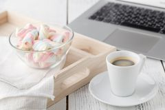 Cup of coffee, twisted marshmallow and laptop notebook Stock Image