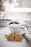 Cup of coffee and two cookies in the shape of a heart against th Royalty Free Stock Photo