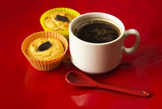 Cup of coffee with two cupcakes on the red background closeup. Royalty Free Stock Photos