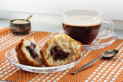 Cup of coffee, two halves cake with stuffing and a spoon. Cup of coffee, two halves of cake with stuffing and a spoon on a beautiful mat royalty free stock photography