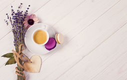Cup of coffee with two macarons, bunch of lavender and wooden heart. Violet and purple concept on white background Stock Images