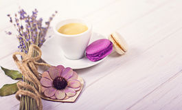 Cup of coffee with two macarons, bunch of lavender and wooden heart. Violet and purple concept on white background Royalty Free Stock Images