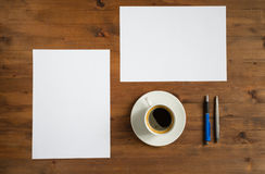 Cup of coffee, two sheets of paper and two pens Royalty Free Stock Photo