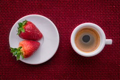 Cup of coffee and two strawberries. On red background. texture royalty free illustration