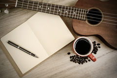Cup of coffee with ukulele and notebook on wooden table Stock Photos