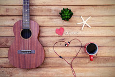 Cup of coffee with ukulele on old wooden Royalty Free Stock Image