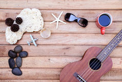 Cup of coffee and ukulele on wooden background Royalty Free Stock Image