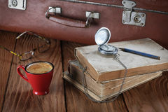 Cup of coffee, vintage suitcase, watches, glasses and old books Stock Photos