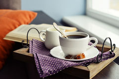Cup of coffee on vintage tray. On sofa with open book stock image