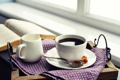 Cup of coffee on vintage tray. On sofa with open book royalty free stock images