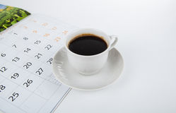 Cup of coffee with wall calendar on white Stock Photography