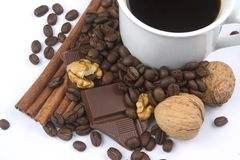 Cup of coffee, walnuts, coffee beans. And bar of chocolate over white background Royalty Free Stock Photos