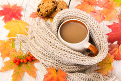 Cup of coffee and warm scarf on a wooden background with autumn Royalty Free Stock Photo