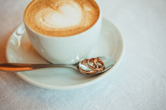 Cup of coffee, wedding rings on table Stock Photography