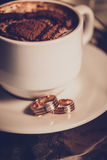 Cup of coffee, wedding rings and wedding bouquet Stock Photo