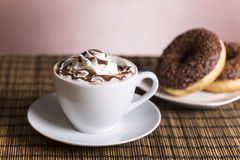 Cup of coffee with whipped cream and chocolate donut with nuts Royalty Free Stock Photography