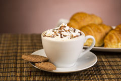 Cup of coffee with whipped cream and croissants Stock Image