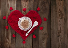Cup of coffee with whipped cream on a red knitted heart. Royalty Free Stock Photos