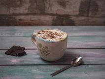 A cup of coffee with whipped cream and sprinkled with grated chocolate, a few chocolate bars lie on a plank of blue tone. Shot from the side royalty free stock images