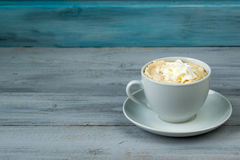 Cup of coffee with whipped cream on wooden background. Cup of coffee with whipped cream on blue and grey wooden background Stock Photography
