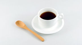 A cup of coffee. A cup of coffee on white background and wooden spoon Stock Image