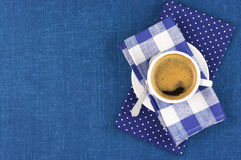 Cup of coffee. White cup of coffee on blue linen. Top view Stock Photo