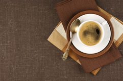 Cup of coffee. White cup of coffee on brown linen. Top view Stock Photography