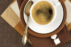 Cup of coffee. White cup of coffee on brown linen. Top view Stock Photos