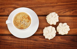 Cup of coffee and white cakes. On wooden background Royalty Free Stock Photos