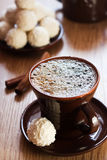 Cup of coffee and white chocolate truffles. On table Royalty Free Stock Photos