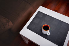 Cup of coffee on a white coffee table in a living room. Concept of lazy afternoon. Royalty Free Stock Image