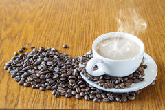 Cup of coffee in a white cup and coffee beans on wooden table ba Stock Photos