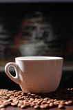 Cup of coffee. White cup of coffee on desk with coffee beans Royalty Free Stock Photo