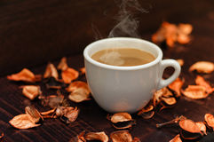 Cup of coffee. White cup of coffee on desk with leaves Royalty Free Stock Image