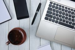 Cup of coffee on the white desktop with a laptop, a notebook, a smartphone and a pen. Business concept.  royalty free stock images