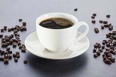 Cup of Coffee in White Cup. Cup of Coffee - cup of espresso or black coffee on a grey background, with coffee beans scattered around. Front to back focus royalty free stock photography